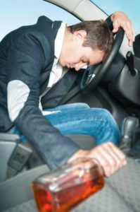 Young driver with bottle in hand sleeps in the car