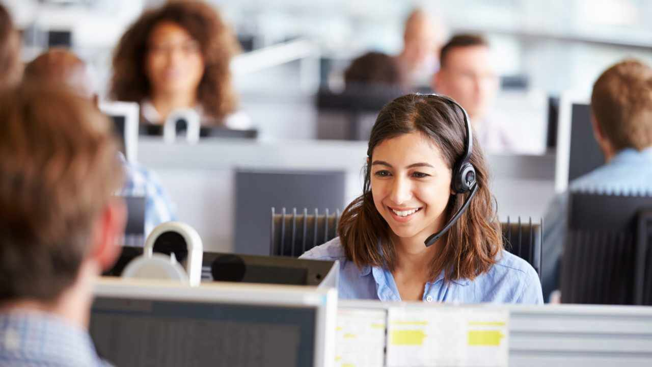 Young woman working in call centre, surrounded by colleagues